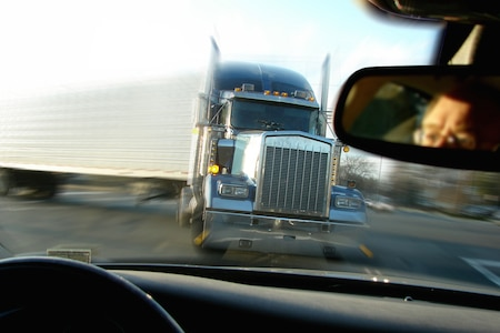 Close call imminent crash accident with a tractor trailer truck viewed from inside a passenger car with scared driver face in rear view mirror